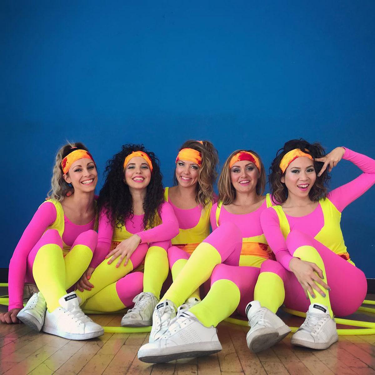 Hula Hoop Dancers wearing colored dancewear sitting at a dance studio