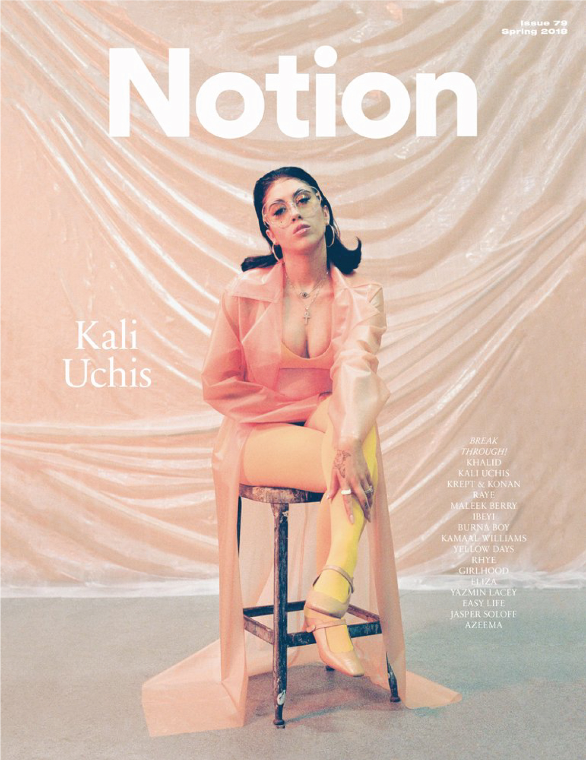 Singer Kali Uchis sitting on a chair with a pink background behind