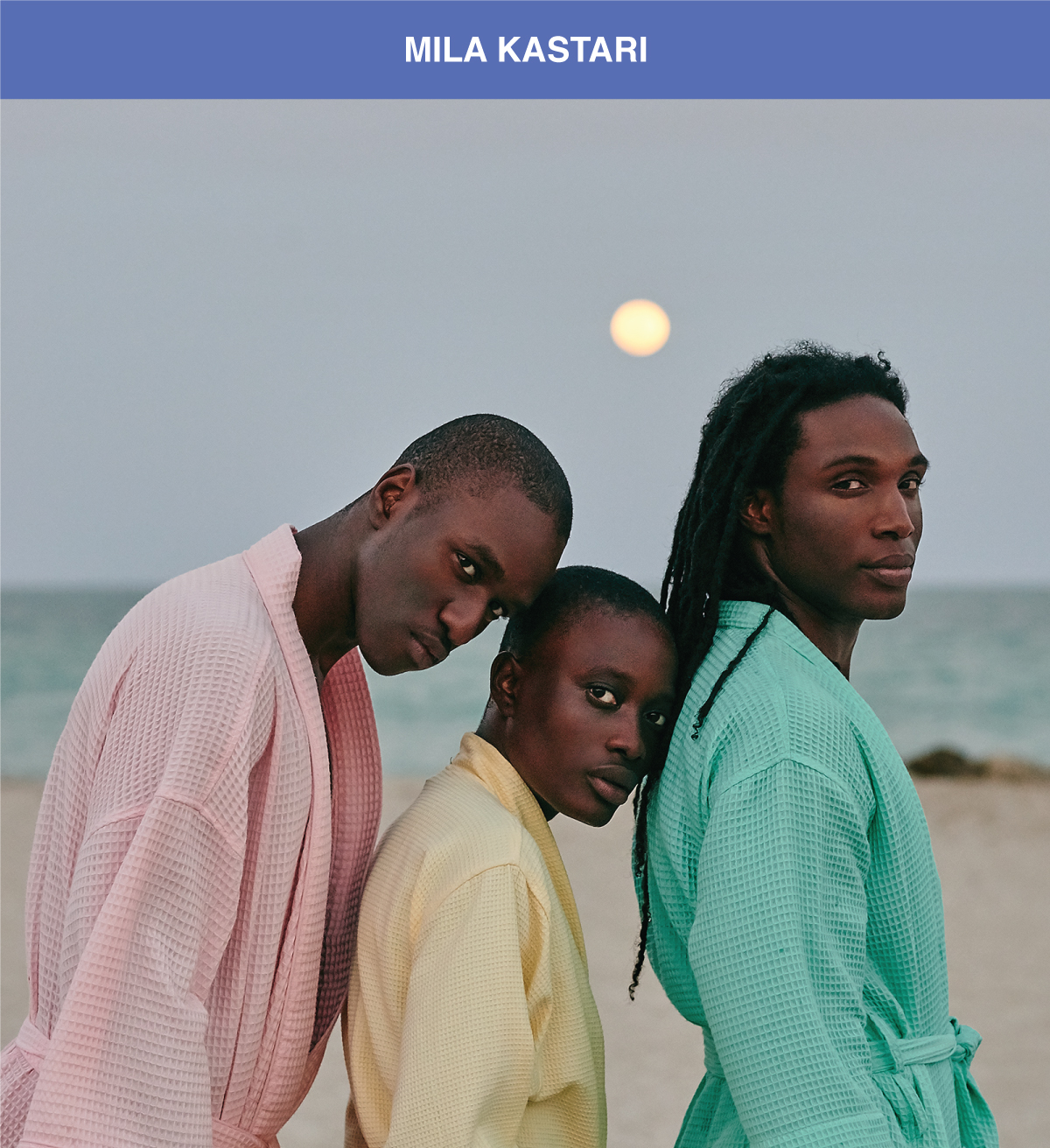 three persons at the beach with pastel color robes