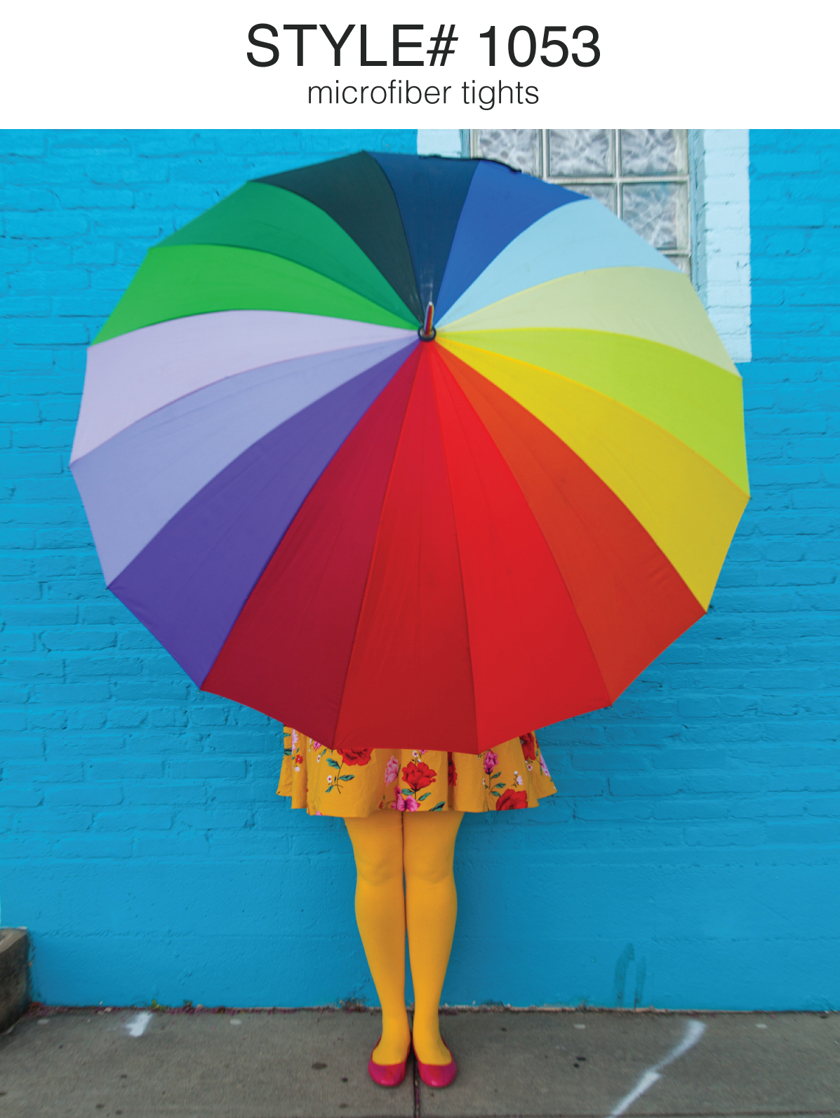 Woman standing against a blue wall holding a rainbow color umbrella and wearing yellow tights