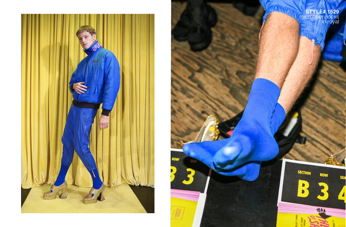 male model posing with yellow curtains behind wearing blue outfit