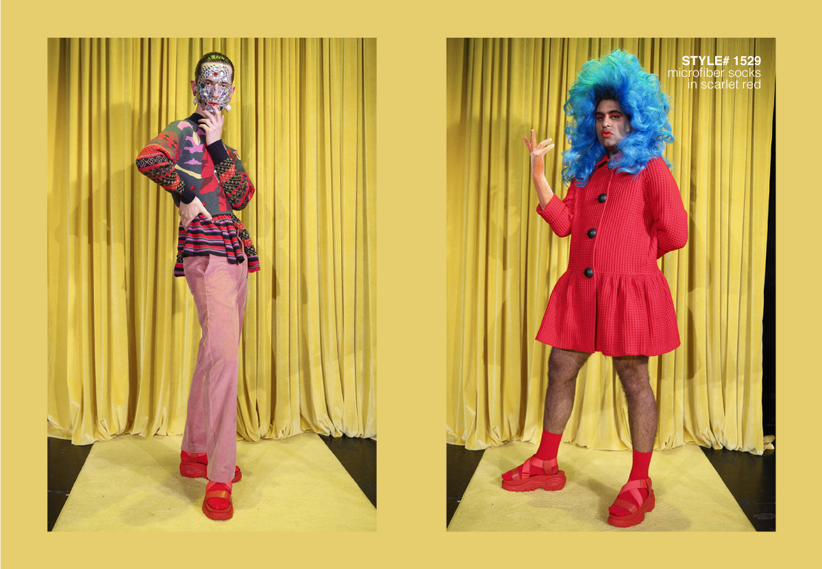 2 male models wearing red and blue outfits stading with yellow curtains behind