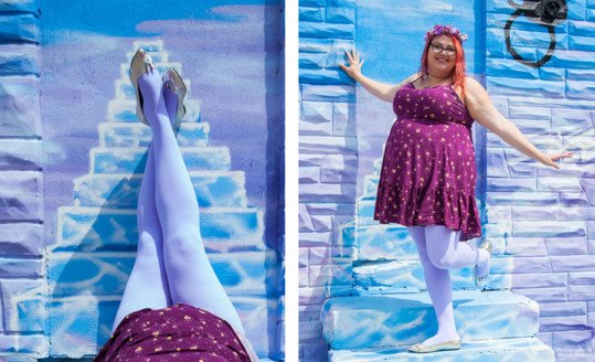 Plus size woman wearing floral print dress and lilac tights standing against a lilac wall