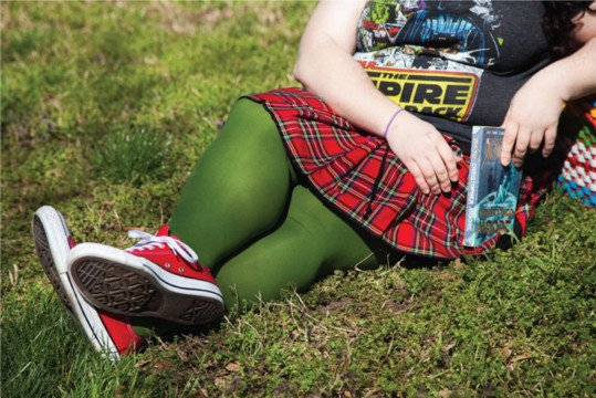 plus size woman laying on the grass wearing a plaid skirt and olive green tights