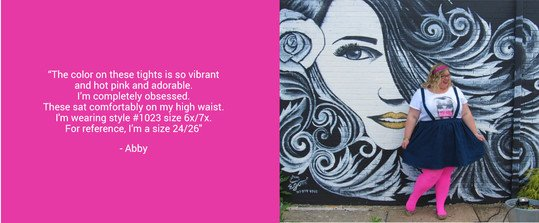 Plus size woman wearing neon pink tights smiling standing against street art wall