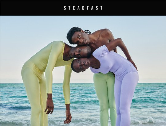 three people standing together wearing unitards and performance tights in pastel colors with ocean in the back
