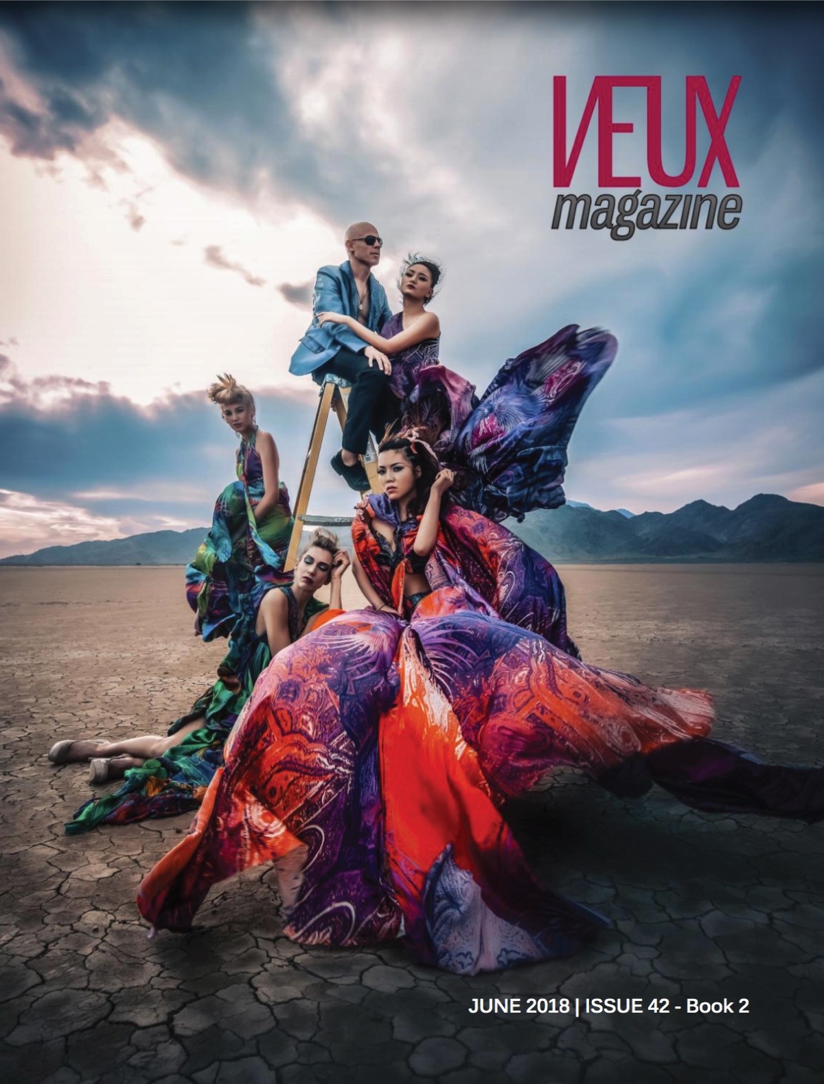 Veux Magazine Cover with four models in colorful big dresses posing in the dessert