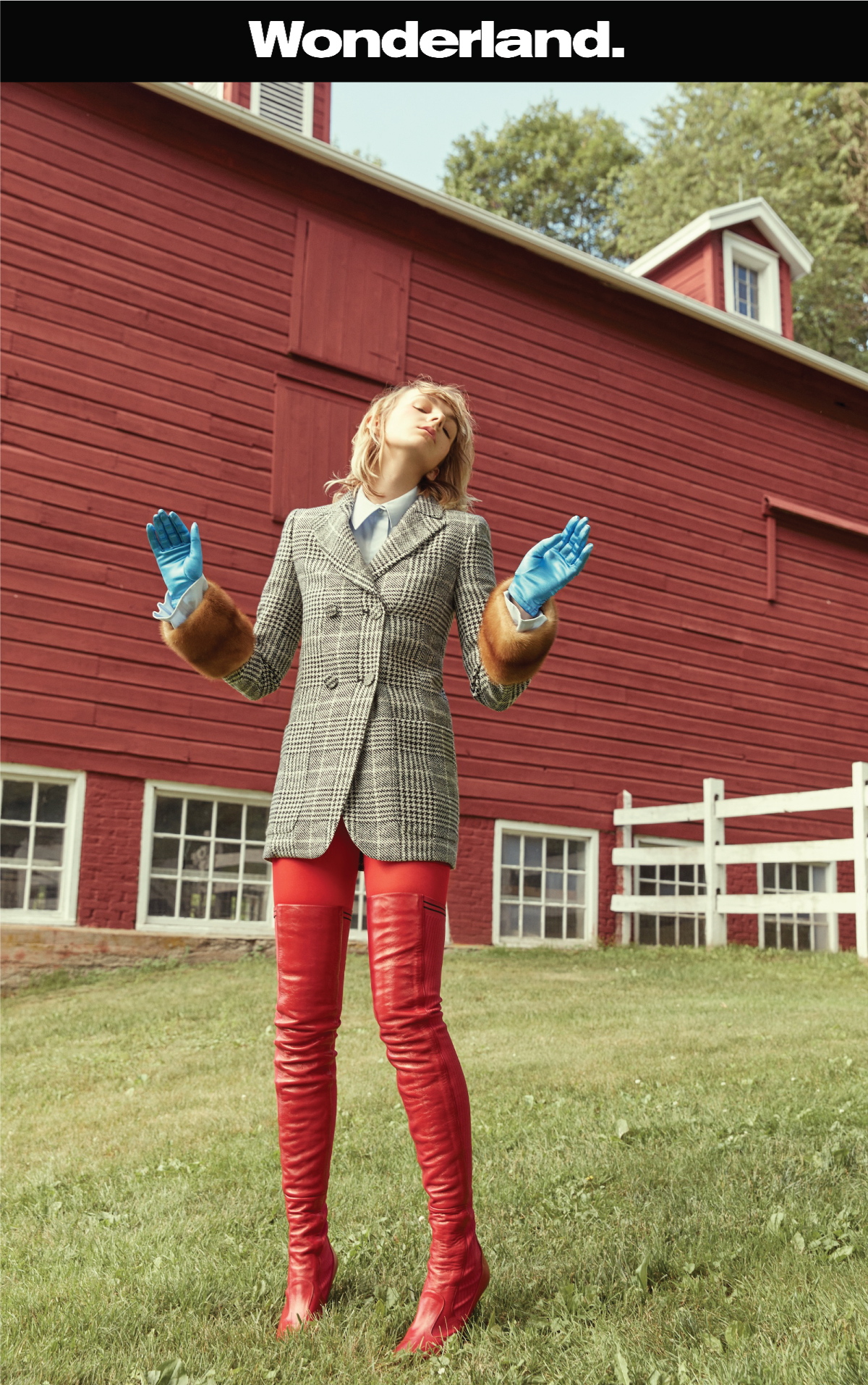 female model standing on the grass with a farm behind