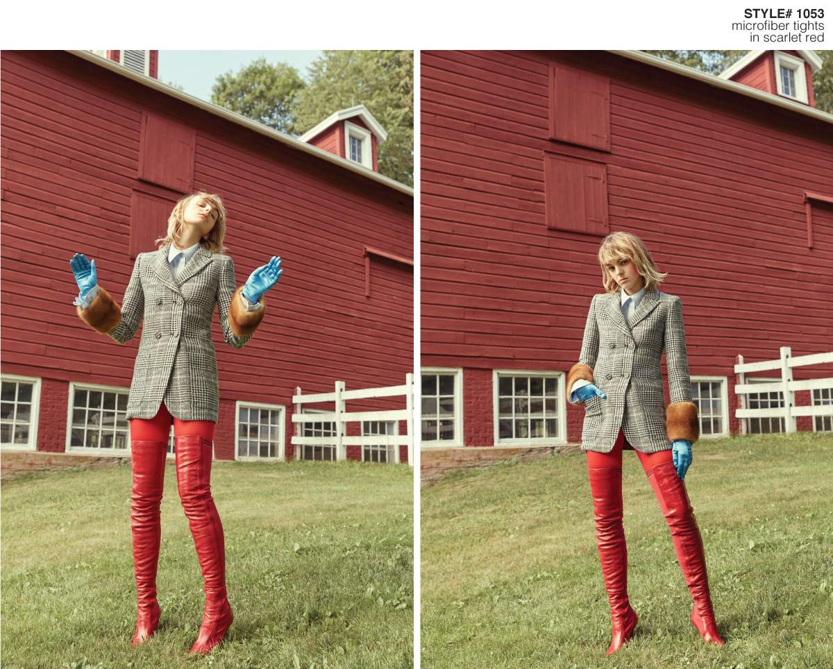 female model standing on the grass with a farm behind wearing red, grey and blue clothes